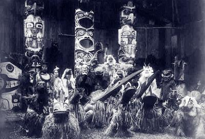 20130622111302-during-the-winter-ceremony-kwakiutl-dancers-wearing-masks-and-costumes-crouch-in-foreground-with-others-behind-them.-the-chief-on-the-far-left-holds-a-speakers-staff.jpg